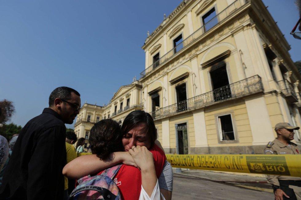 Хората пред изгорелия музей плачат и се прегръщат в опит да се утешат взаимно. Снимка: EFE