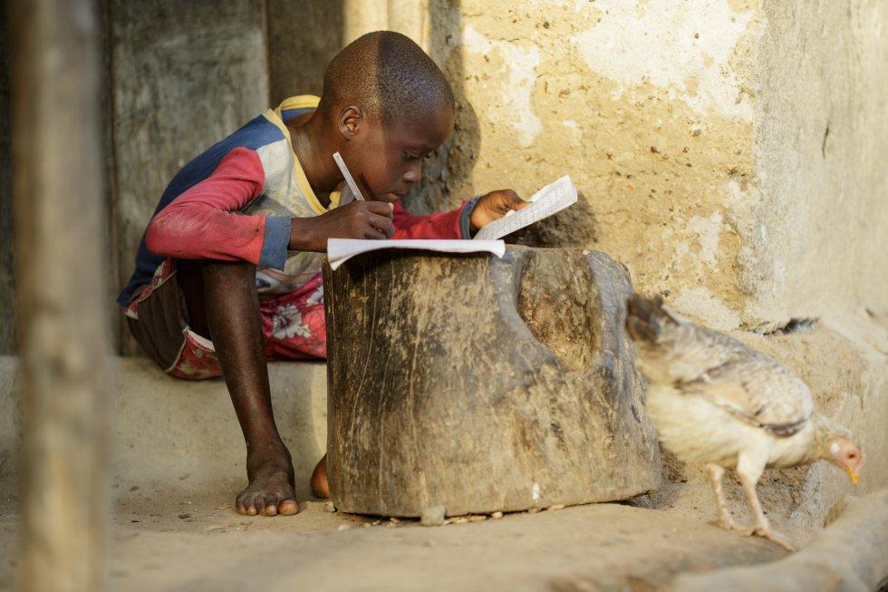 Дете от Сиера Леоне пише домашните си на дръвник пред дома си в село Матене. Снимка: УНИЦЕФ