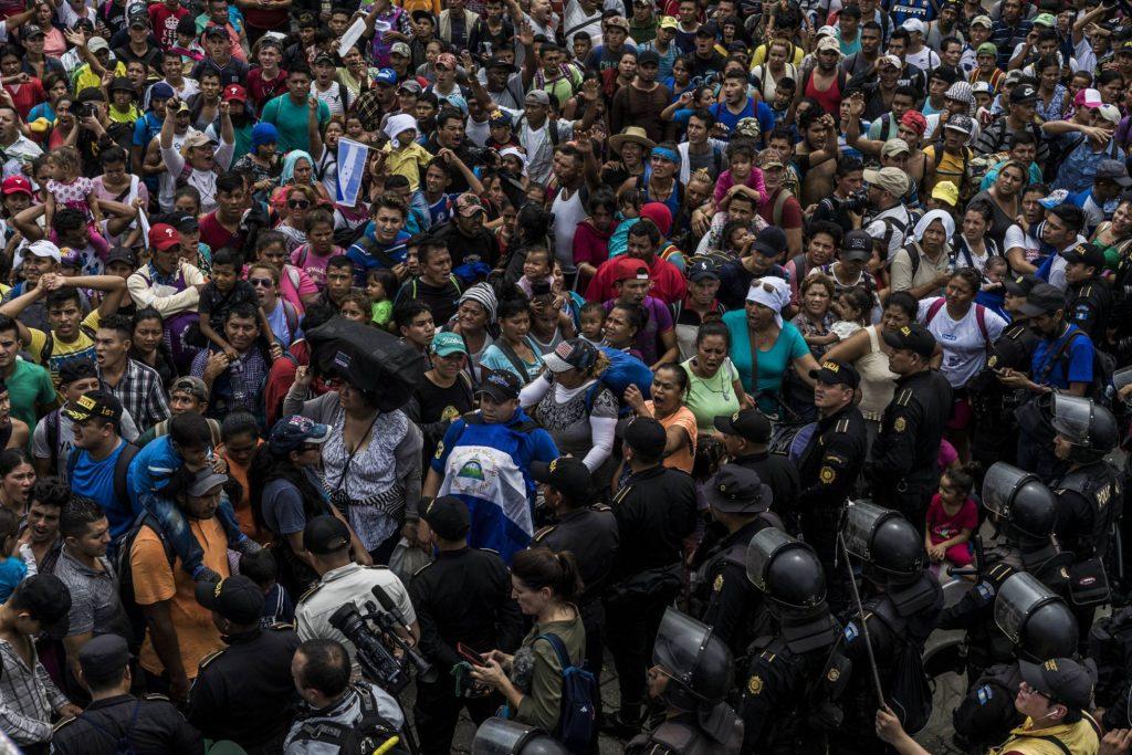 Участници в шествието и мексикански полицаи на гватемалско-мексиканската граница. Снимка: El Pais