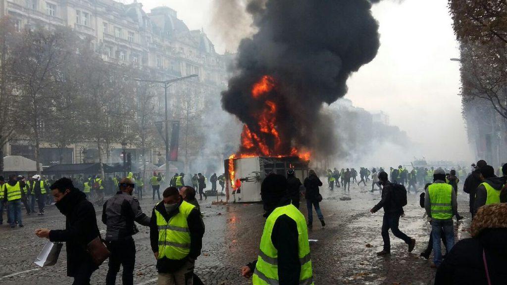 """Будка гори в средата на """"Шанз Елизе"""" по време на протеста на """"жълтите жилетки"""" срещу поскъпването на горивата. Снимка: Туитър"""
