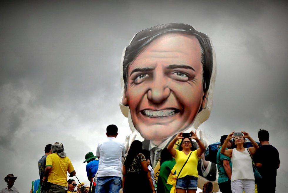 Привърженици на Болсонаро си правят селфита пред балон с неговия лик преди началото на речта му на Площада на трите власти в град Бразилия. Снимка: EFE