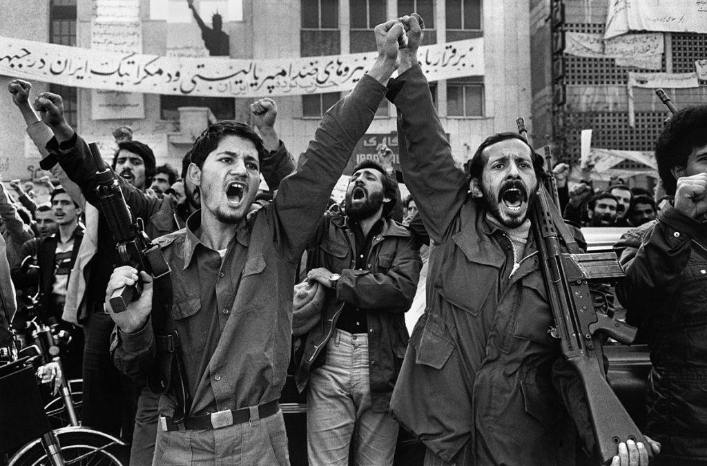 """Въоръжени мъже, участващи в демонстрация в Иран през 70-те. Зад тях се вижда лозунг, гласящ """"""""да живее антиимпериализма и демократичните сили"""". Wikimedia Commons"""
