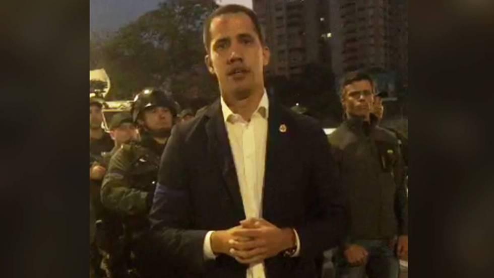 Хуан Гуайдо в кадър от видеозаписа, в който зове за преврат. Зад него вдясно е Леополдо Лопес. Отляво се виждат демонстративно подредени военни. Снимка: El Pais