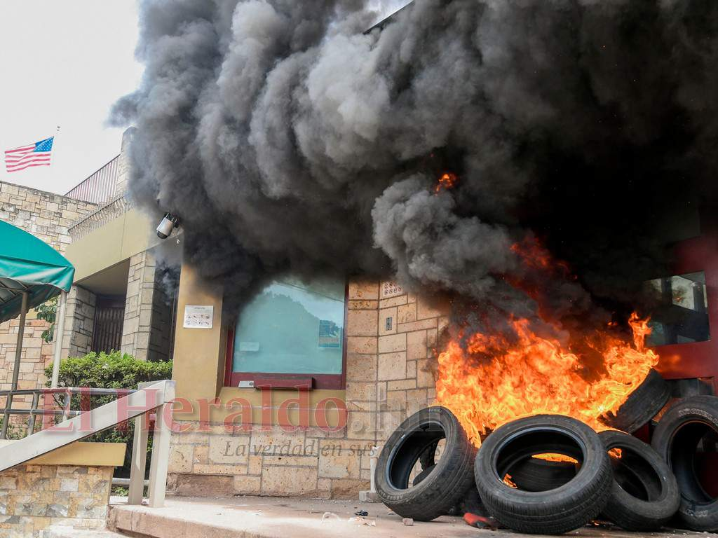 Пламъци и пушек се издигат от нахвърлени пред входа в оградата около американското посолство в Тегусигалпа подпалени автомобилни гуми. Снимка: El Heraldo
