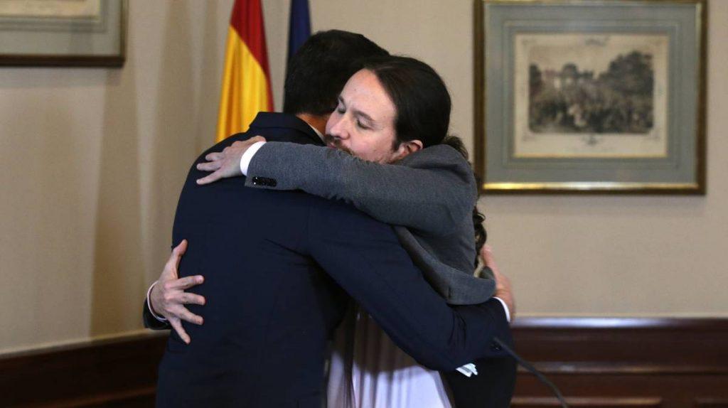 """Педро Санчес и Пабло Иглесиас запечатаха с прегръдка подписаното днес от тях предварително споразумение за """"прогресивна коалиция"""". Снимка: El Pais"""