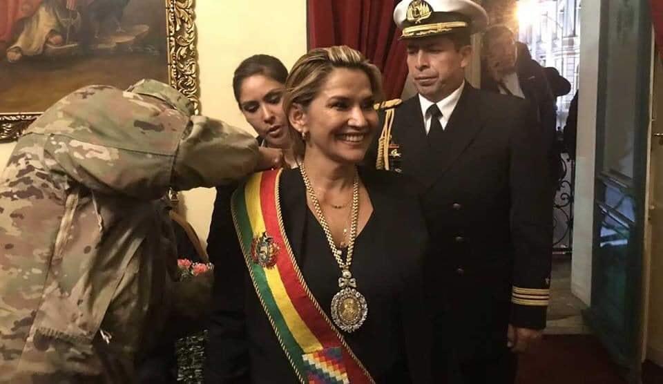 Жанин Аниес се радва на президентската лента, която й закачват военните по време на фарсовата церемония в Сената при липсващ кворум. Снимка: Фейсбук