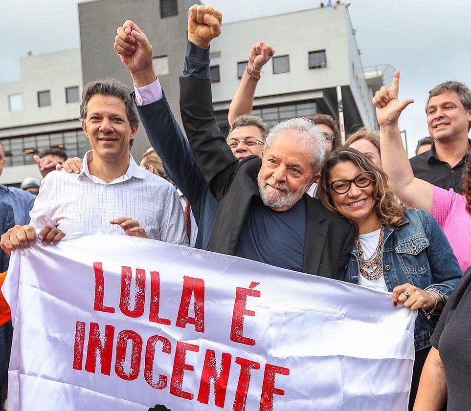 Лула непосредствено след излизането му от затвора в Куритиба. От едната му страна е Фарнандо Адада, който бе кандидат на Работническата партия в президентските избори в Бразилия през 2018 г., а от другата му страна е неговата любима - социоложката Розанжела да Силва. Снимка: Рикардо Стукерт