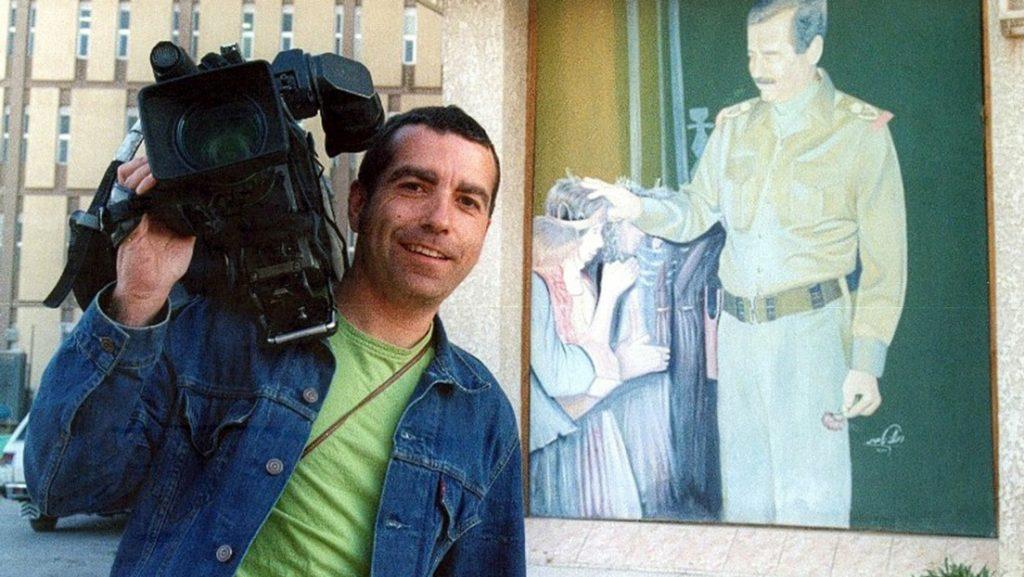 """Испанският телевизионен оператор Хосе Коусо с камерата си край портрет на Саддам в Багдад, броени дни преди да бъд убит от американски обстрел по хотел """"Палестина"""". Снимка: Туитър"""