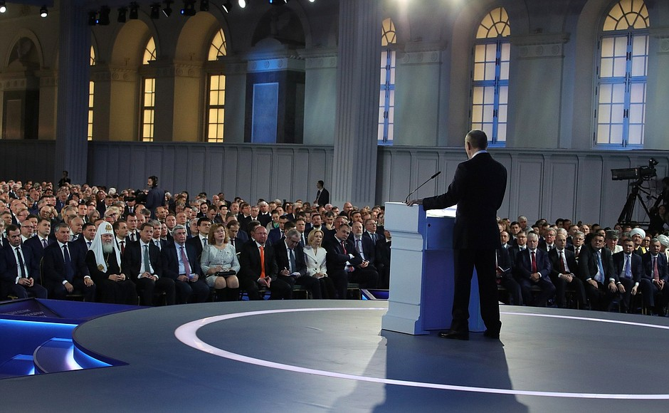 Руският президент Владимир Путин (в гръб) по време на обръщението си към Федералното събрание. Снимка: kremlin.ru