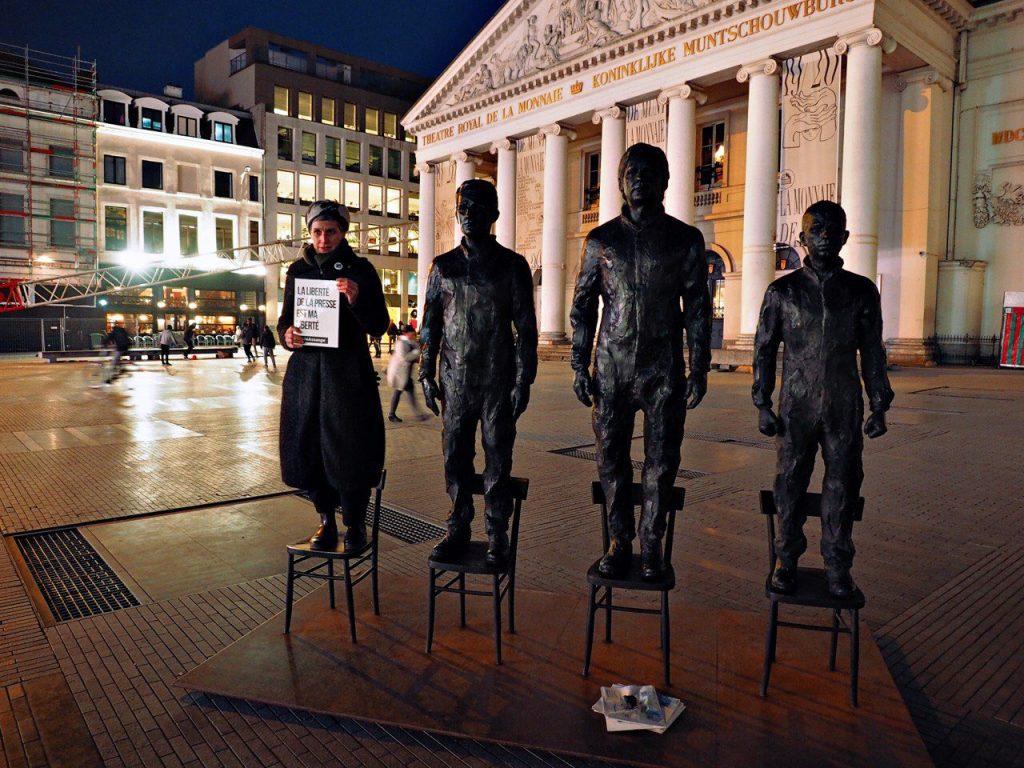 """""""Свободата на пресата е моята свобода,"""" пише на плаката, който държи участничка в акцията в защита на Асанж в центъра на Брюксел. Жената е заела четвъртият стол от скулптурната композиция """"Anything to Say?"""", изобразяваща Сноудън, Асанж и Манинг. Тя бе инсталирана на площад """"Моне"""", временно преименуван в площад """"Асанж"""". Снимка: Туитър"""