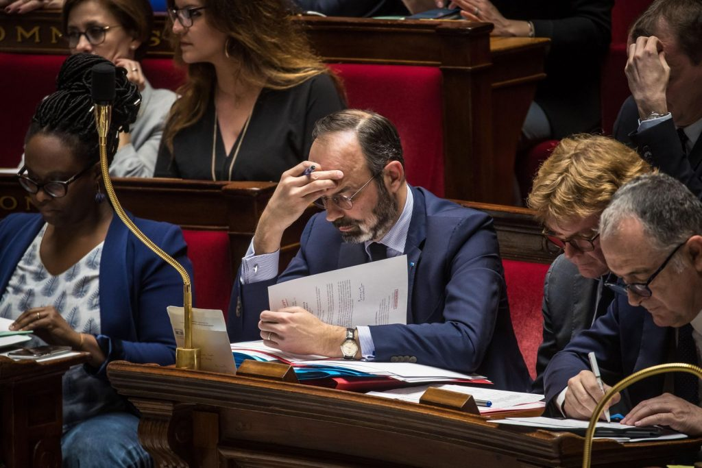 С ръка на челото и зачетен в документи, френският премиер Едуар Филип изслуша доста нехайно дебатите около двата вота на недоверие към кабинета му. Той лесно ги спечели и така прокара през конституционна вратичка също и пенсионната реформа на първо четене. Снимка: EFE