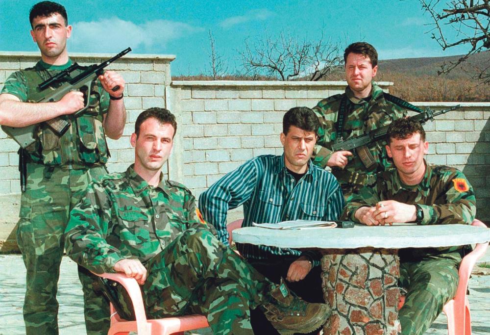 Хашим Тачи (цивилният в центъра) сред бойци на АОК по време на войната в Косово. Снимка: alo.rs