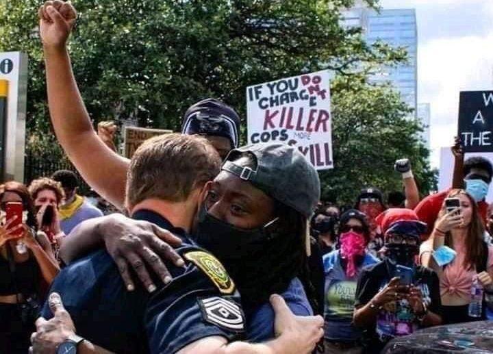 Чернокож демонстрант и бял полицай се прегръщат по време на протестите против расизма и социалното неравенство в Маями, САЩ. Снимка: Туитър