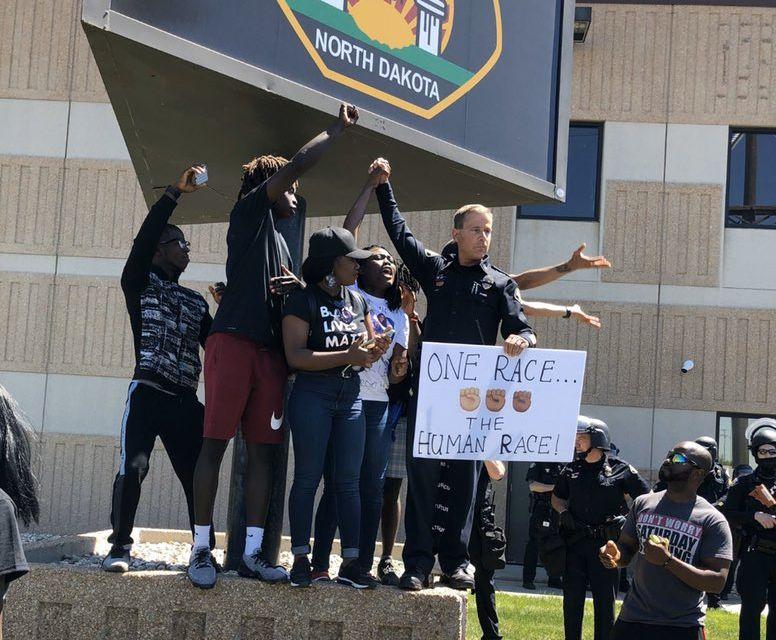 """На все повече места в САЩ полицаи се присъединяват към демонстрантите в антирасистките им протести. Този кадър е заснет пред полицейски участък в Северна Дакота, чийто началник държи заедно с протестиращи плакат с надпис: """"Една раса - човешка раса"""". Снимка: Туитър"""