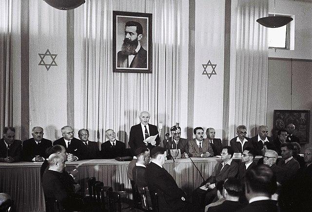 Давид Бен-Гурион обявява създаването на държавата Израел под портрет на основателят на модерния политически ционизъм Теодор Херцел. Източник: Wikimedia Commons