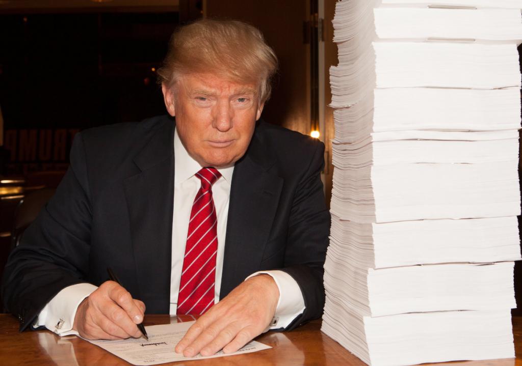 Тръмп подписва иронично данъчните си декларации, за които сега става ясно, че са пълни със съмнителни схеми за укриване на данъци.