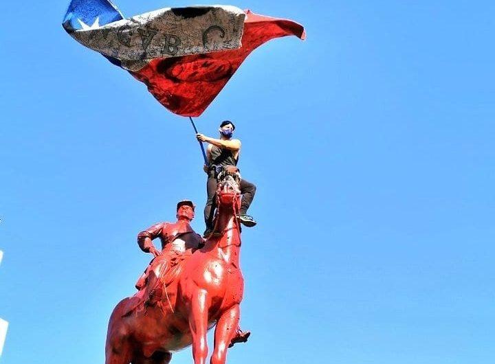 Протестиращ, покачен върху паметника на генерал Бакедано в чилийската столица Сантяго. Снимка: resumenlatinoamericano.org