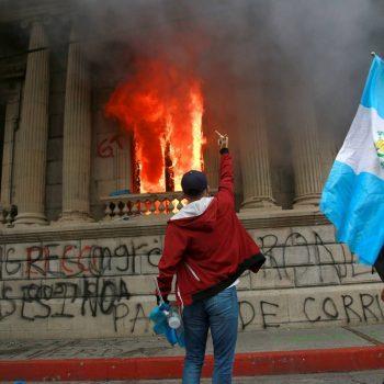 Млад демонстрант изразява гнева си пред вече подпаления от маскирани Конгрес в столицата на Гватемала. Снимка: EFE