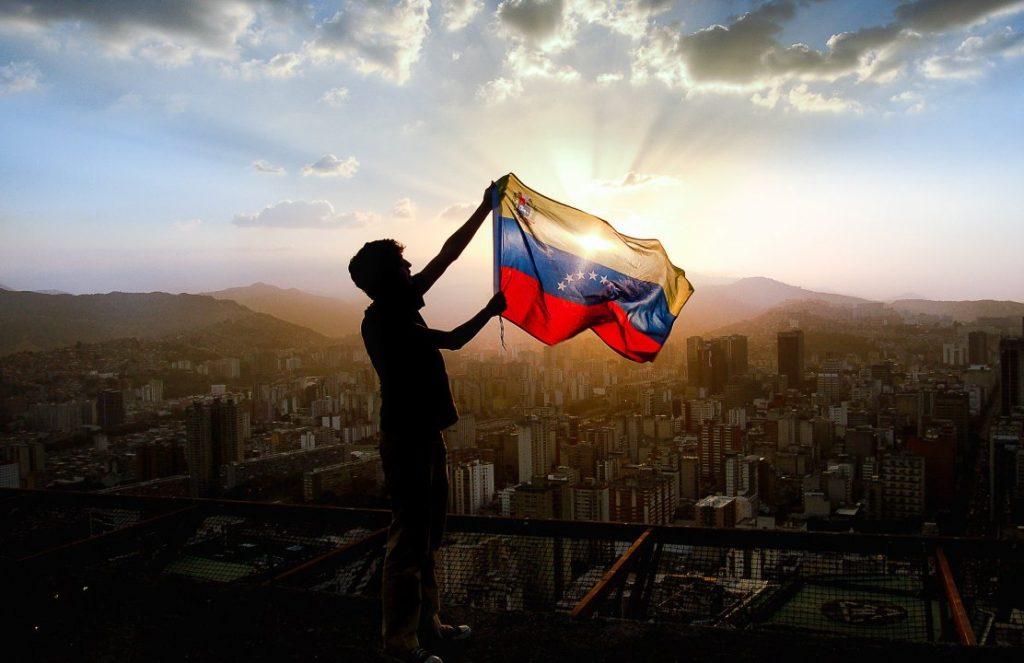 Венесуелец развява националното знаме над Каракас от инсталация на лифта, водещ към планината Уарайра Репано. Снимка: nodal.am