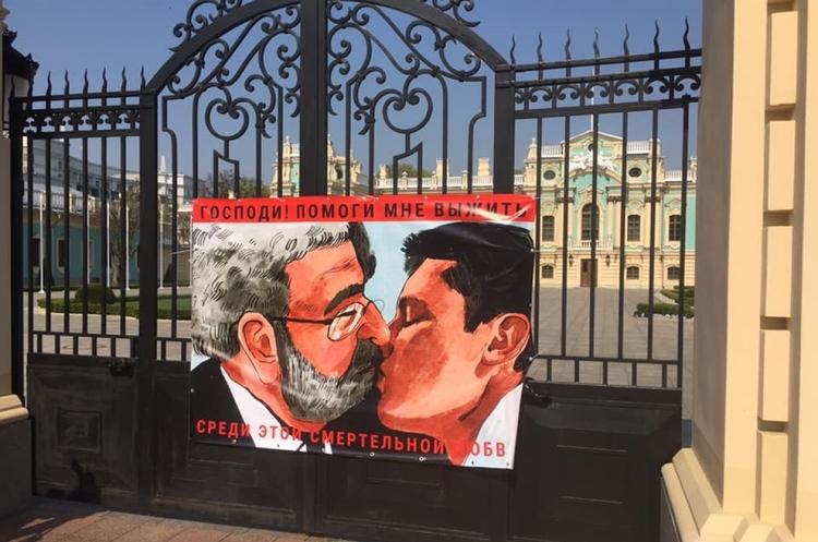 """""""Господи, помогни ми да се спася сред тази смъртоносна любов!"""" - пише на плакат с портретите на целуващите се Коломойски и Зеленски, появил се през 2019 г. на портата на президентската резиденция в Киев. Снимка: mind.ua"""