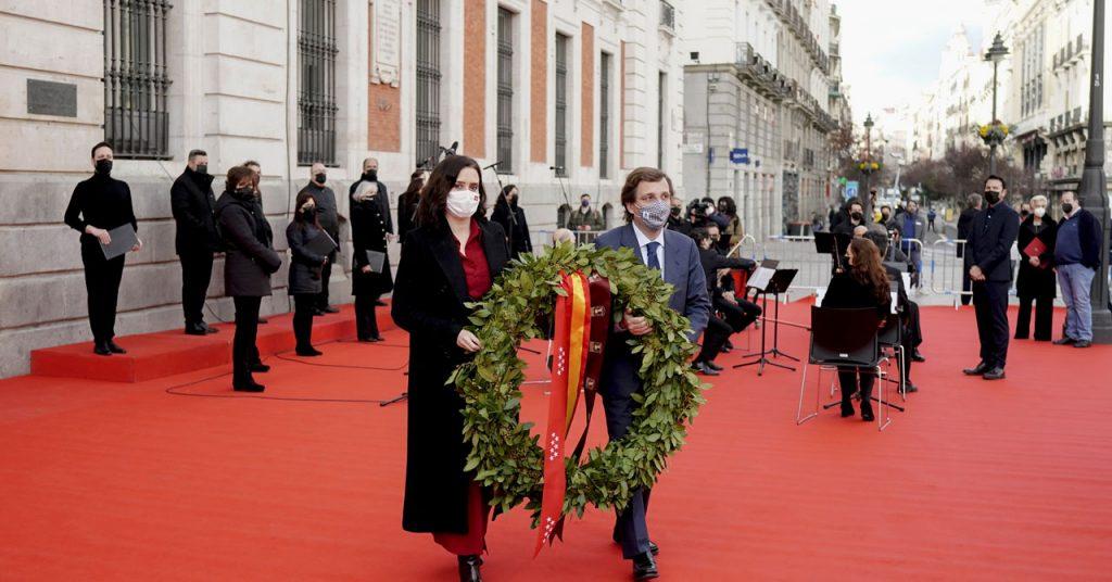 """Президентката на Автономна област Мадрид Исабел Диас-Аюсо и мадредският кмет Хосе Луис Мартинес-Алмейда поднасят венец пред паметната плоча на площад """"Пуерта дел Сол"""" в памет на жертвите от атентата на 11 март 2004 г. Зад тях е Оркестърът и хорът на Автономна област Мадрид, а вдясно стои изправен в тъмен костюм ръководителят на музикалната формация - българският маестро Кръстин Настев. Снимка: fuenlabradanoticias.com"""