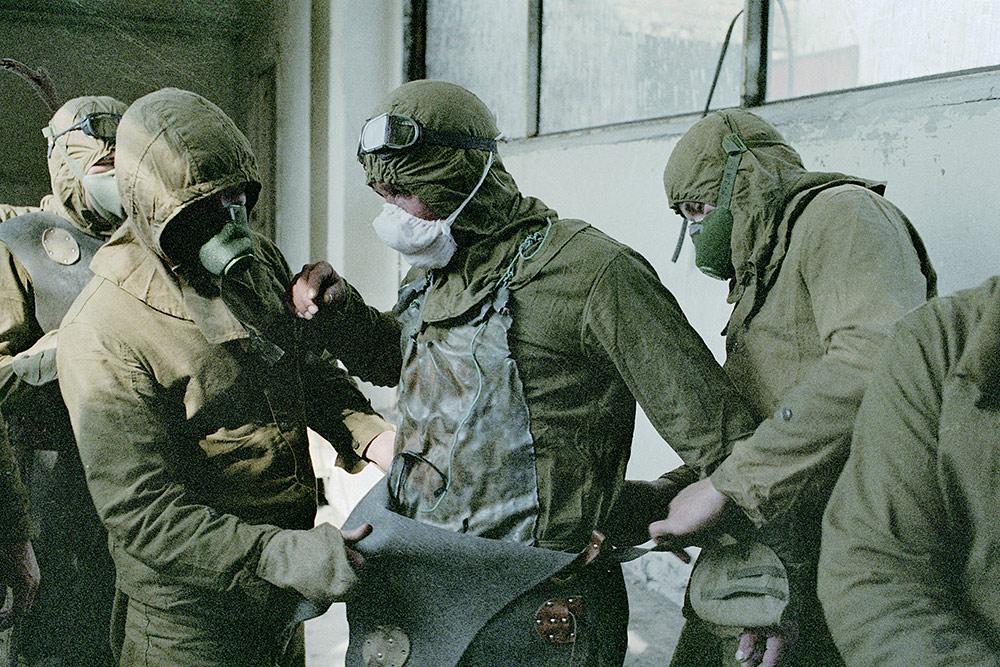 Ликвидатори на последствията от аварията в Чернобилската АЕЦ запасват свой другар с оловна престилка преди да го пуснат в най-опасната зона. Снимка: gazeta.ru