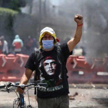 Демонстрант на преградена от барикада улица в колумбийския град Кали. Снимка: EFE