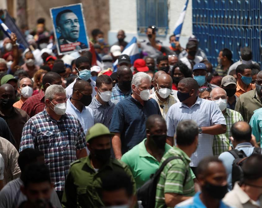 Президентът на Куба Мигел Диас-Канел (в центъра, със синя риза и бяла маска) обиколи улиците на град Сан Антонио де лос Баньос, където през уикенда много хора излязоха на протести, притеснени от режима на тока и скока в заразяването с Ковид-19. Снимка: granma.cu